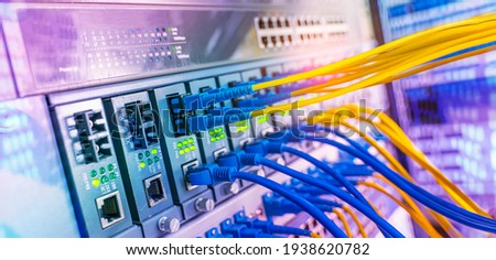 Fiber Optical cables connected to an optic ports and Network cables connected to ethernet ports Royalty-Free Stock Photo #1938620782