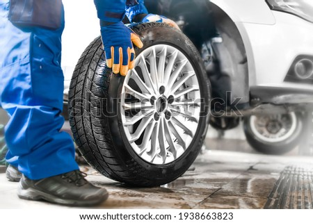 Car mechanic working in garage and changing wheel alloy tire. Repair or maintenance auto service. Royalty-Free Stock Photo #1938663823