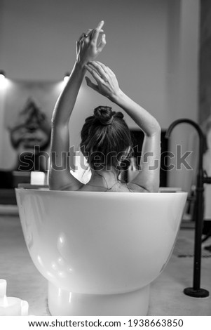 Young woman relaxing in the beautiful vintage bath full of foam in the retro bathroom decorated with candles Royalty-Free Stock Photo #1938663850
