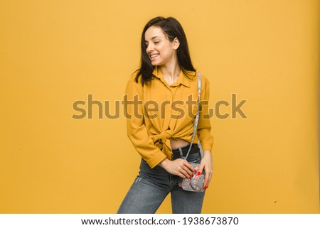 Concept photo of young female with purse, smiling and looks happy. Wears yellow shirt, isolated yellow color background