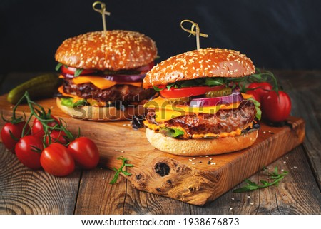 Two delicious homemade burgers of beef, cheese and vegetables on an old wooden table. Fat unhealthy food close-up. Royalty-Free Stock Photo #1938676873