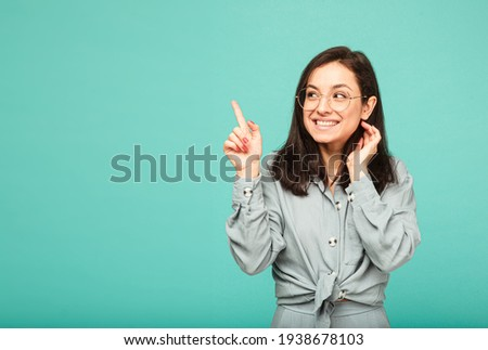 Photo of cute female in glasses smiles nicely and point finger up. Wears grey shirt, isolated turquoise color background