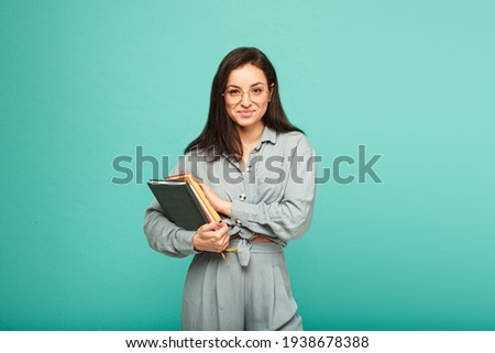 Photo of cute female holds books and smile. Wears grey shirt, isolated turquoise color background