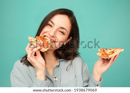 Photo of cute lady eats pizza, enjoy junk food. Wears grey shirt, isolated turquoise color background
