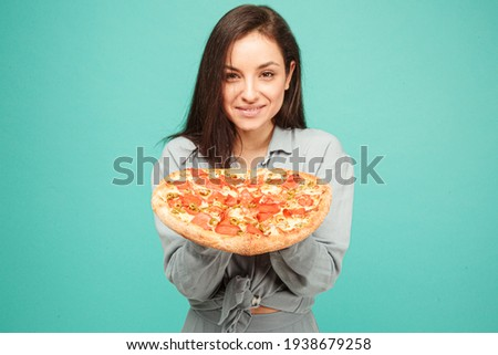 Photo of cute lady holds pizza, enjoy junk food. Wears grey shirt, isolated turquoise color background