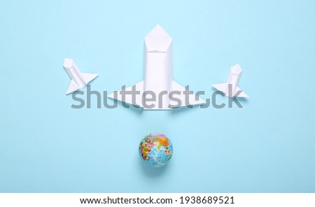 Origami space rocket shuttles and globe on blue background. Space flight concept