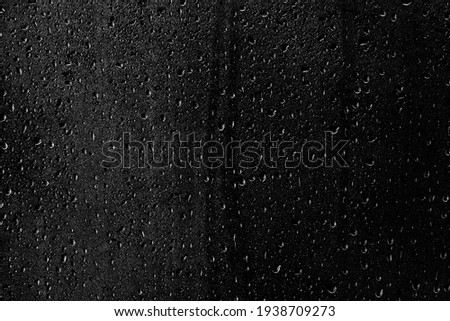Drops of water flow down the surface of the clear glass on a black background. Texture for creativity. Royalty-Free Stock Photo #1938709273
