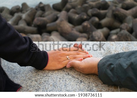A picture of hand of a man holding his partner's hand showing love and affection at Marine drive, Mumbai.