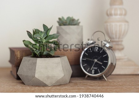 Concrete decorative flower pot and metal clock on the work table. desk layout. Decorative items on the office table. Decorative flower pot, book and clock Royalty-Free Stock Photo #1938740446