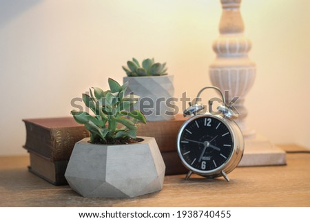 Concrete decorative plant pot and metal clock on the work table. Decorative items on the office table. Decorative flower pot, book and clock Royalty-Free Stock Photo #1938740455