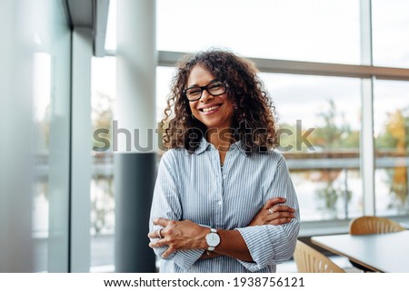 Portrait of successful female professional with her arms crossed. Smiling businesswoman standing in office. Royalty-Free Stock Photo #1938756121