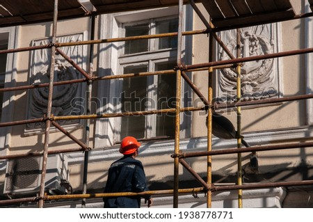 Man builder in orange construction helmet working from scaffolding to renovate historic building wall with ornate sculptural relievo details. Historic building restoration in progress Royalty-Free Stock Photo #1938778771