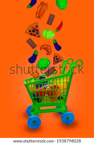 ToyShopping cart with different toy food falling in den Shopping cart,Background color orang. Royalty-Free Stock Photo #1938798028