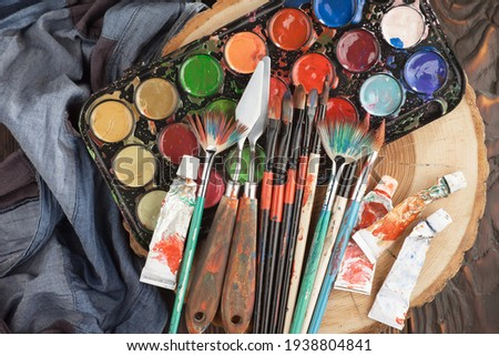Brushes and paints for painting on an old background. Royalty-Free Stock Photo #1938804841