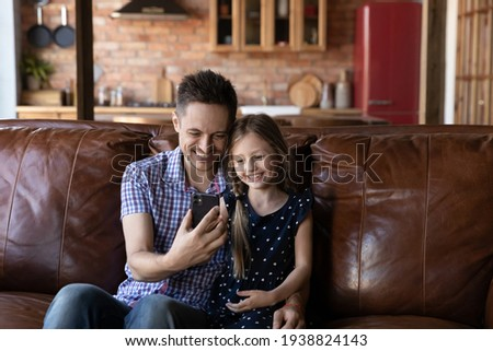 Say cheese, dad. Lovely little girl sitting on couch close to happy millennial father embracing and taking selfie on mobile phone, making video call together, watching funny cartoon online by wifi