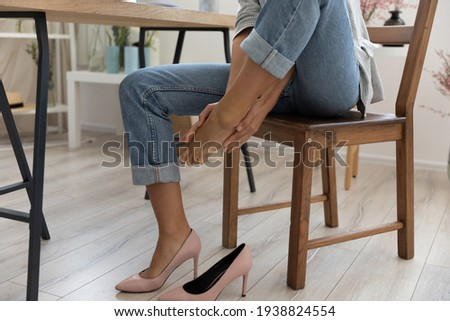 Crop close up of businesswoman sit at desk in office take off uncomfortable heels shoes suffer from legs pain ache. Female employee touch massage feet, feel discomfort in foot, have strained muscles. Royalty-Free Stock Photo #1938824554