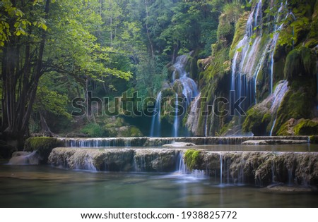 """magnificent waterfall called """"cascade of tuffs"""" in the Jura in France in the middle of a forest. This waterfall is a protected natural site. Royalty-Free Stock Photo #1938825772"""