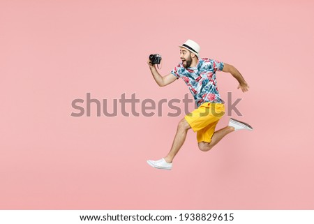 Full length traveler tourist man in summer clothes hat jumping taking pictures on retro vintage photo camera isolated on pink background. Passenger traveling on weekends. Air flight journey concept