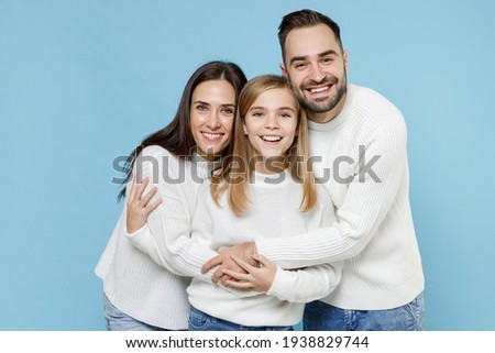 Laughing funny young happy parents mom dad with child kid daughter teen girl in basic white sweaters hugging isolated on blue color background studio portrait. Family day parenthood childhood concept