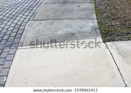 Patrially cleaned and partial irty cement sidewalk in front of a homeafter some of it has been pressure washed. Royalty-Free Stock Photo #1938865411