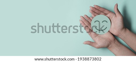 Hand holding green paper cut smile face on green background, positive thinking, mental health assessment , world mental health day concept Royalty-Free Stock Photo #1938873802