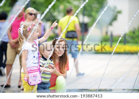 Woman with children  near fountain in spring park #193887413