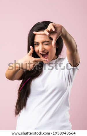 Beautiful Indian woman making a hand frame over pink background, composing picture ideas