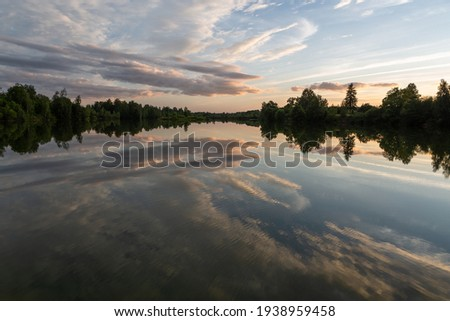 Cloudscape in summer at sunset on the lake and field Royalty-Free Stock Photo #1938959458