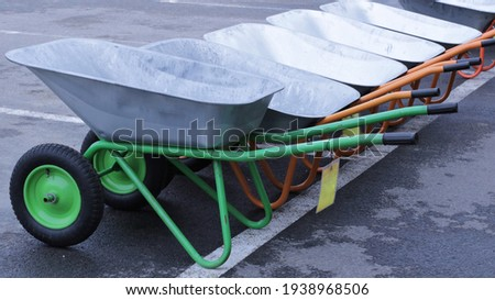 several new two-wheeled carts on sale at the beginning of the garden spring season, garden and building hand tools in a specialized store, tools for gardening and construction