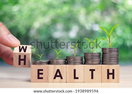 Hand flip wooden cube with word wealth to health with coins stack step up growing growth value. Investment in life insurance and healthcare concept Royalty-Free Stock Photo #1938989596