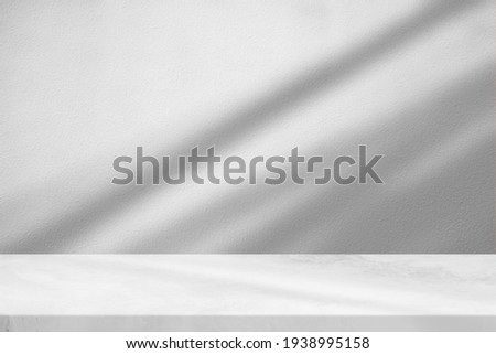 Marble Table with White Stucco Wall Texture Background with Light Beam and Shadow, Suitable for Product Presentation Backdrop, Display, and Mock up. Royalty-Free Stock Photo #1938995158