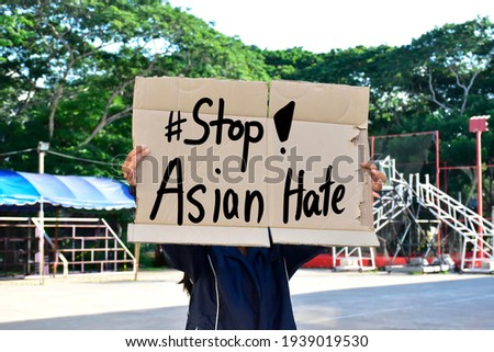 Asian female holds a paper sign with English words '#Stop Asian Hate', concept for calling the international community to stop the hatred of the Asian people that has caused spreading of the covid-19. Royalty-Free Stock Photo #1939019530