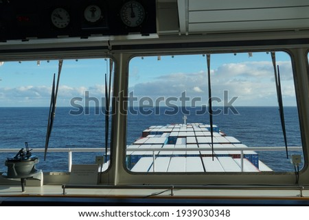 View form the window  of the navigational bridge of the container vessel on the containers covered with snow underway through Pacific ocean during calm sea. Royalty-Free Stock Photo #1939030348