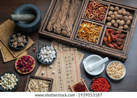 Ancient Chinese medicine books and herbs on the table.English Translation:Traditional Chinese medicine is used in the prevention and treatment of diseases, has the function of rehabilitation. Royalty-Free Stock Photo #1939053187