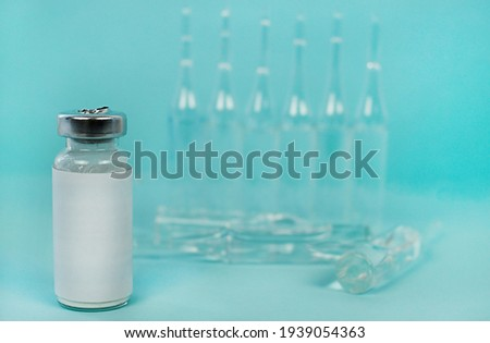 A glass jar with a label on the background of empty ampoules. flasks with the vaccine in the background. place for caption and inscription. the photo is applicable in science and medicine.