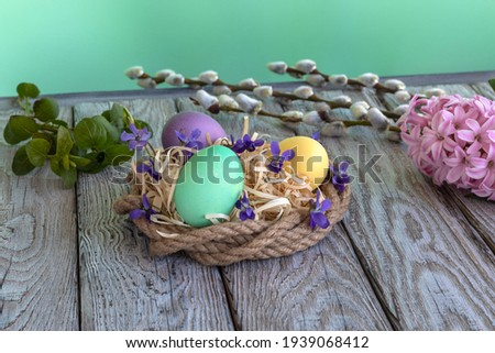 Colorful Easter Greeting Card in style of Provence: easter eggs in makeshift nest made of rough jute rope, wood shavings, and decorated with cute violets. On background of emerald wall.