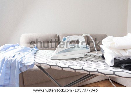 Steam blue iron on ironing board. Clothes, ironing board household concept Royalty-Free Stock Photo #1939077946
