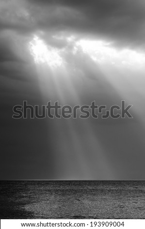 Amazing ray of light shines through storm clouds over ocean #193909004