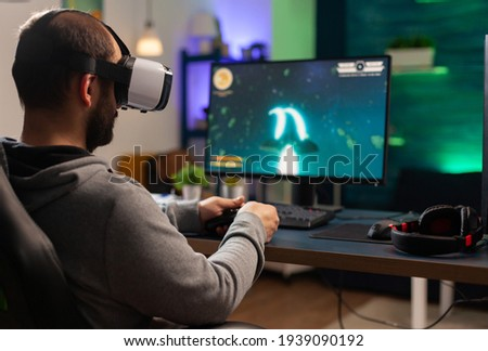 Competitive gamer playing e-sport championship using technology network wireless Professional man wearing vr headset and play online space shooter competition on powerful computer Royalty-Free Stock Photo #1939090192