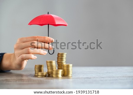 Young woman hand holding small red umbrella over pile of coins on table. Close up of stack of coins with female hands holding umbrella for protection. Financial safety and investment concept.   Royalty-Free Stock Photo #1939131718
