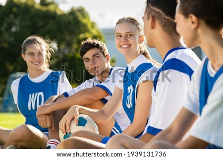 Happy football players sitting on grass on playground field before match. Mixed school soccer players talking during break. Guys and girls teammates sitting in a row for physical education lesson. Royalty-Free Stock Photo #1939131736