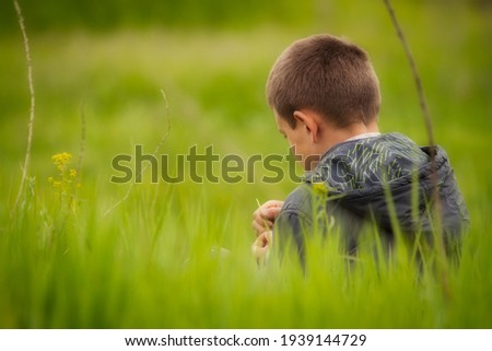 a photographic image of a boy in a jacket with a hood close-up on the right side of the composition sits on the grass with his back, his face half turned and holds a blade of grass in his hands. Royalty-Free Stock Photo #1939144729