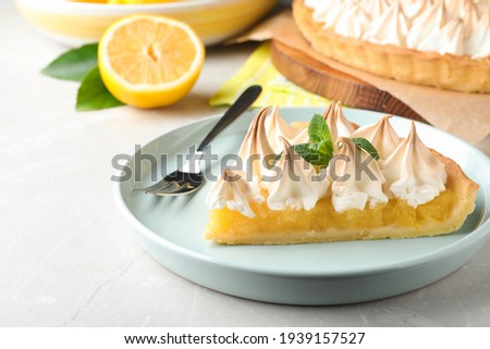 Piece of delicious lemon meringue pie with mint served on light table, closeup