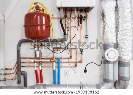Heating installation and central boiler heating system on wall in house close-up Royalty-Free Stock Photo #1939198162