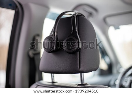 on-ear headphones hang on the headrest in the car. technology personal multimedia system in a modern premium car. no poeole Royalty-Free Stock Photo #1939204510