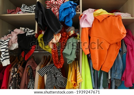 Messy wardrobe with different clothes. Fast fashion concept Royalty-Free Stock Photo #1939247671