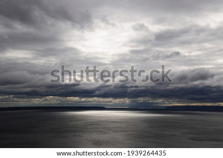 Panorama of the lake before the rain. Thunderclouds over the lake. Royalty-Free Stock Photo #1939264435