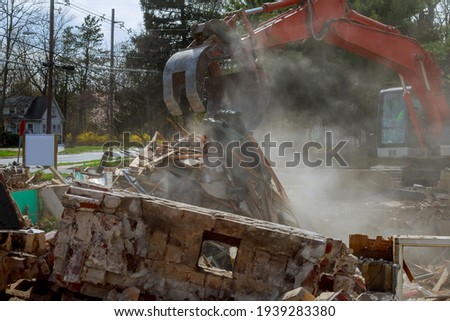Excavator demolishing of the house after the hurricane urban regeneration broken house after tragedy Royalty-Free Stock Photo #1939283380