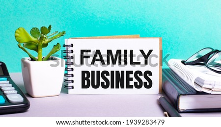FAMILY BUSINESS is written on a white card next to a potted flower, diaries and calculator. Organizational concept