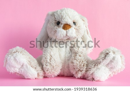 Stuffed bunny on pink background. Easter concept. Cute toy bunny sitting on colored background. Royalty-Free Stock Photo #1939318636